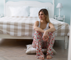 Portrait of sad young woman in bedroom